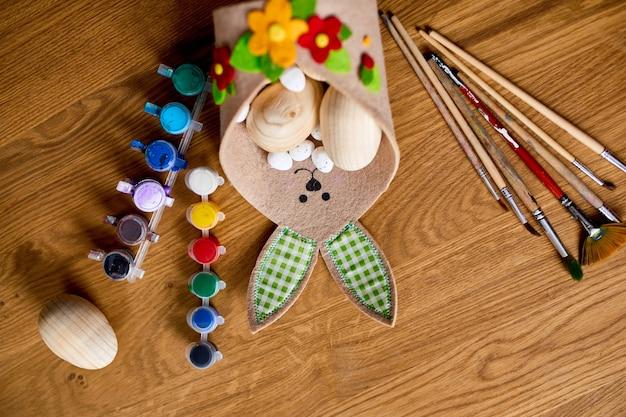 Confezione vista dall'alto di uova con pennello, vernice ed elementi decorativi su fondo in legno. copia spazio, buona pasqua, fai da te, laici piatta. Foto Premium