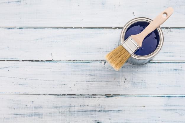 Vernice dall'alto con colore blu e pennello sul tavolo.
