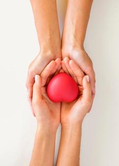 Vista dall'alto del paio di mani che tengono a forma di cuore con cura