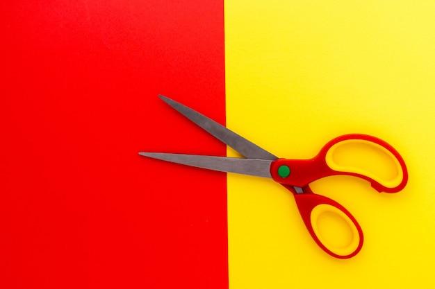 Vista dall'alto della coppia di forbici aperte in plastica con lama in acciaio inossidabile su sfondo rosso-giallo. strumento per il taglio di vari materiali sottili. lay piatto, copia dello spazio.
