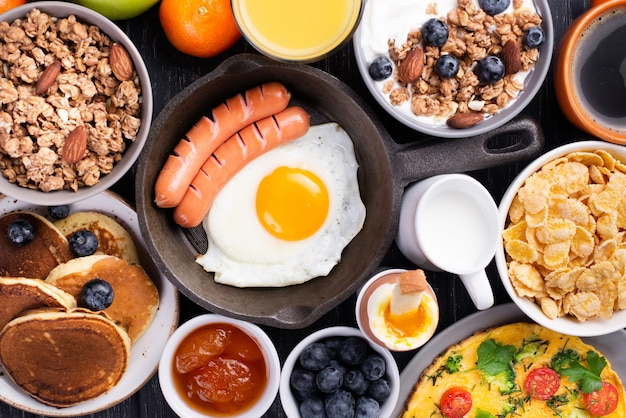 Vista dall'alto di frittelle con uovo e salsicce per la colazione Foto Premium