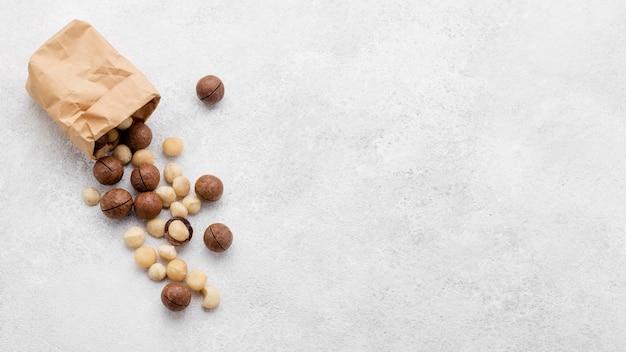 Sacchetto di carta vista dall'alto riempito con noci di macadamia e spazio copia cioccolato