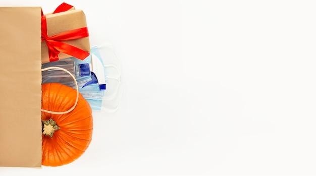 Sacchetto di carta vista dall'alto con zucca fresca, scatole regalo, maschere antisettiche e antivirus. shopping per halloween o il ringraziamento. bandiera. disposizione piatta. copia spazio.