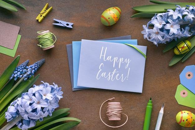 Vista dall'alto di carte di carta, fiori di giacinto blu e uova di pasqua sul buio