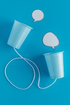Vista dall'alto di bicchieri di carta con corde e bolle di chat