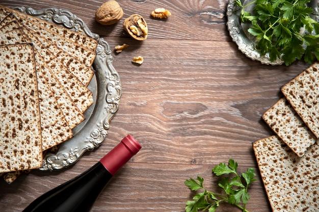 Vista dall'alto dello sfondo di pasqua. celebrazione della pasqua ebraica con vino e pane azzimo sullo sfondo di legno.