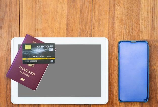 Vista dall'alto passaporto con carta di credito e tavoletta digitale mock up sulla scrivania in legno