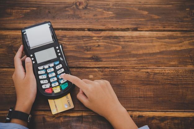 Vista dall'alto pagamento con carta di credito, acquisto e vendita di prodotti utilizzando una macchina per lo scorrimento delle carte di credito