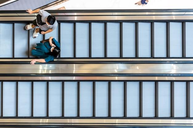 Vista dall'alto di persone sulla scala mobile all'interno del centro commerciale