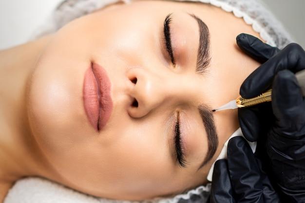 Vista dall'alto del trucco permanente sulle sopracciglia della giovane donna caucasica con uno speciale strumento tatuaggio