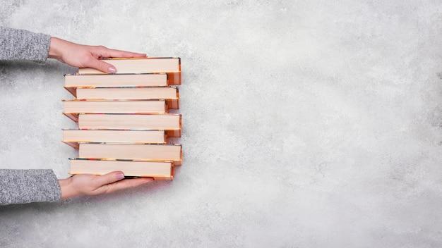 Vista dall'alto della persona in possesso di libri con copertina rigida impilati con spazio di copia