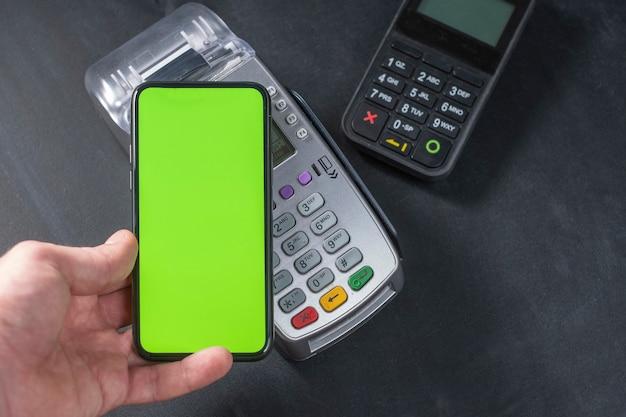 Vista dall'alto della persona che utilizza il pagamento senza contatto con lo smartphone