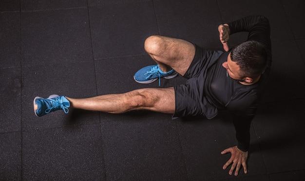 Foto vista dall'alto di un bell'uomo barbuto che fa esercizi di yoga in palestra. immagine ad alta risoluzione.