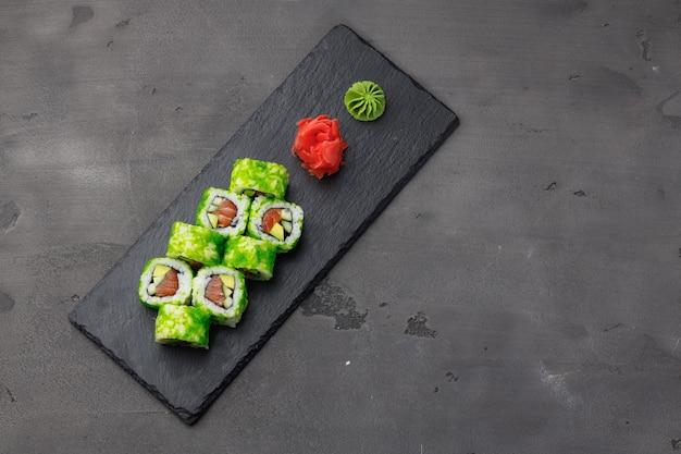 Foto di vista dall'alto del rotolo di sushi della california nella piastra su sfondo nero