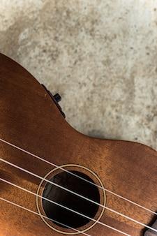 Foto di vista superiore del foro audio alto vicino delle ukulele sul pavimento di cemento.