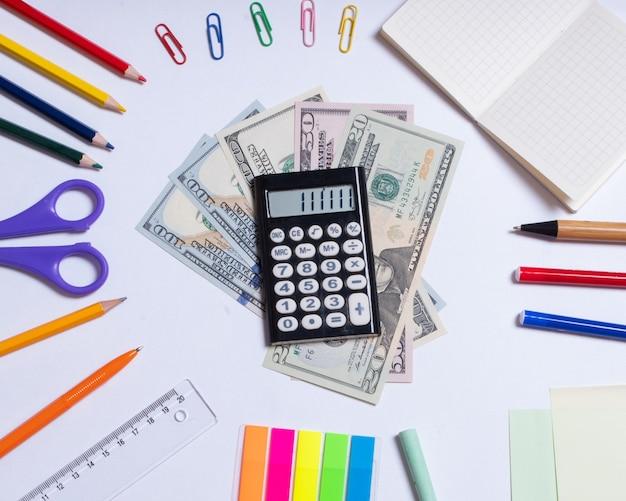 Vista dall'alto di una foto di dollari e una calcolatrice al centro e forniture per ufficio colorate, isolate su una superficie bianca.