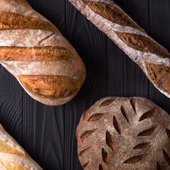 Foto vista dall'alto di pane appena sfornato sul tavolo di legno nero verniciato.