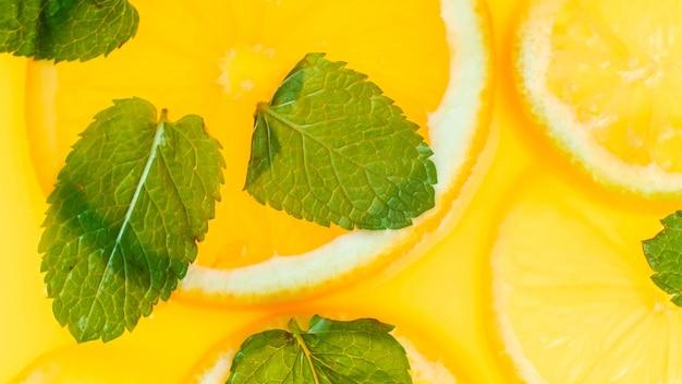 Foto vista dall'alto di succo d'arancia fresco con fette di frutta e foglie di menta.