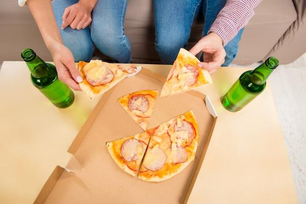 Foto vista dall'alto dell'uomo e della donna che mangiano pizza con la birra