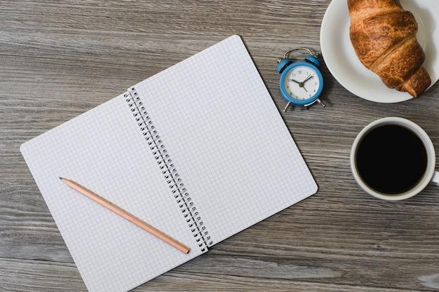 Foto di vista superiore della tazza aperta della sveglia della matita del pianificatore e del croissant sulla zolla isolata