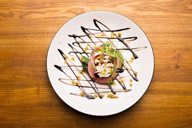 Foto vista dall'alto di un piatto con un panino al prosciutto splendidamente decorato.