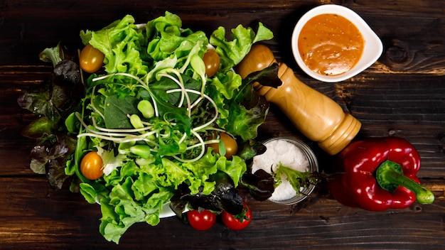 Foto vista dall'alto di insalata con una varietà di tipi di verdure naturali in una ciotola di legno su fondo di legno. idea menu sano e dietetico.