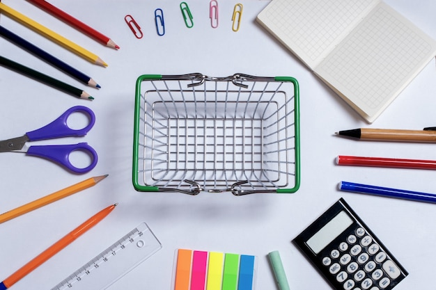 Foto vista dall'alto di un piccolo carrello della spesa al centro e forniture per ufficio colorate, isolate su una superficie bianca