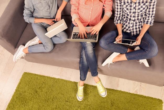 Foto vista dall'alto di tre ragazze che lavorano su laptop e tablet digitale