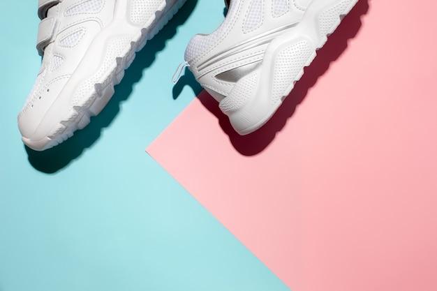 Vista dall'alto pezzi di scarpe da ginnastica bianche sul lato su un delicato sfondo geometrico rosa e blu di carta...