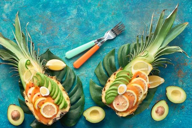 Vista dall'alto su barche di ananas con fette di salmone affumicato e avocado con limone e uova di quaglia, piatto giaceva su sfondo a trama