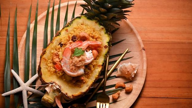 Vista dall'alto del riso fritto all'ananas (kao pad sapparod) in una ciotola di ananas tagliata sul vassoio in legno