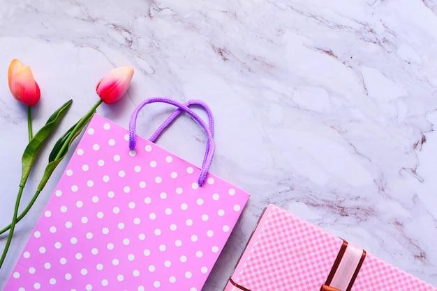 Vista dall'alto della confezione regalo di colore rosa e fiore sul tavolo.