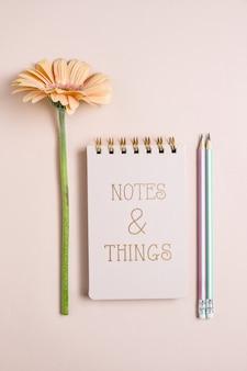 Vista superiore del notepade rosa con pensils e gerbera fresca flowerr sulla superficie pastello rosa. copia spazio, composizione verticale