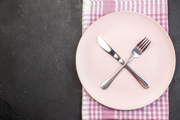 Vista dall'alto piatto rosa con forchetta e coltello su sfondo scuro