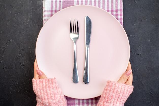 Piatto rosa vista dall'alto con forchetta e coltello sulla superficie scura