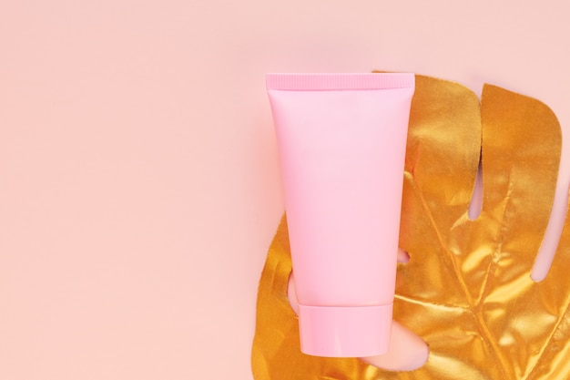 Vista dall'alto di un tubo rosa di mockup crema con una foglia di monstera dorata su uno sfondo rosa. pacchetto cosmetici senza marchio.