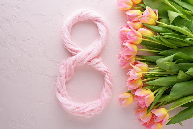 Tulipani rosa vista dall'alto con tonalità gialla su sfondo rosa con tessuto numero otto per la giornata internazionale della donna l'8 marzo, concetto della giornata della donna
