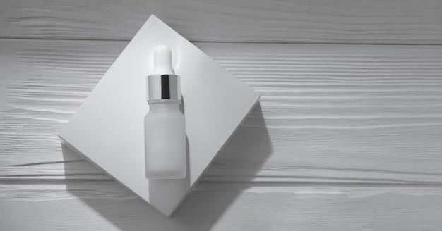 Vista dall'alto della bottiglia della pipetta sulla scatola bianca su una superficie di legno con lo spazio della copia