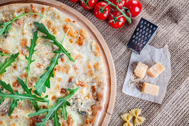 Formaggio della pizza quattro di vista superiore con la rucola su fondo di legno. cucina italiana. snack e fast food. foto di cibo orizzontale. pizza con ingridients sul tavolo. deliziosa pizza con spazio di copia