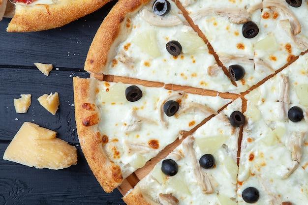 Pizza vista dall'alto con pollo, ananas e olive. pizza hawaiana su fondo di legno scuro con copia sapce. pizza italiana con carne sfondo di cibo. gustosa pizza fatta in casa con cucina italiana