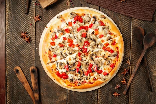 Vista dall'alto sulla pizza con funghi e pomodori sul tavolo di legno