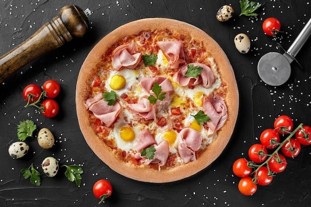 Vista dall'alto della pizza con uova di quaglia e prosciutto?