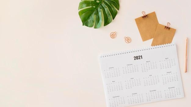 Calendario planner vista dall'alto con spazio copia foglia monstera