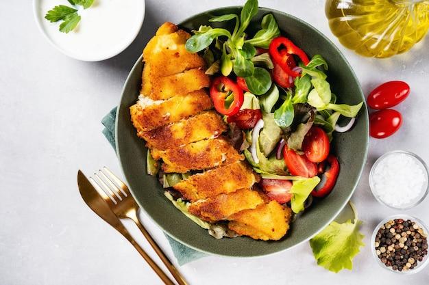 Vista dall'alto di un piatto con delizioso merluzzo impanato con insalata sana