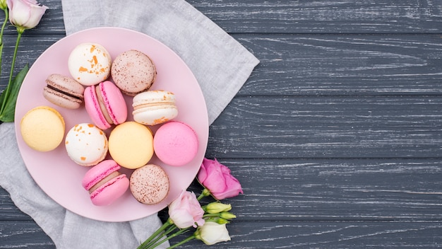 Vista dall'alto del piatto con macarons e rose