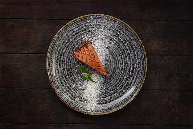 Vista dall'alto del piatto con un pezzo di torta al cioccolato su fondo in legno