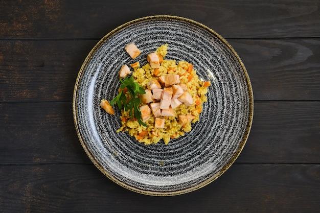 Vista dall'alto del piatto con risotto con prosciutto e carota sul tavolo di legno scuro