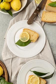 Vista dall'alto di piatti con fetta di torta al limone e foglie