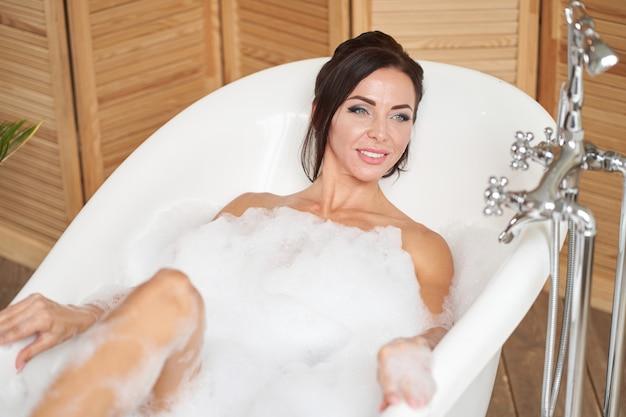 Vista dall'alto. donna piacevole che prende piacere nel bagno di bolla