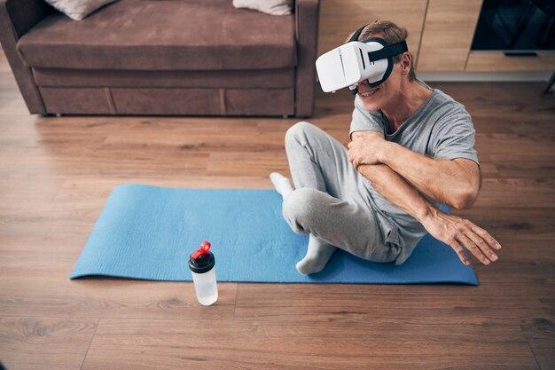 Vista dall'alto di un uomo maturo soddisfatto seduto in posa yoga mentre fa esercizi durante l'allenamento virtuale a casa
